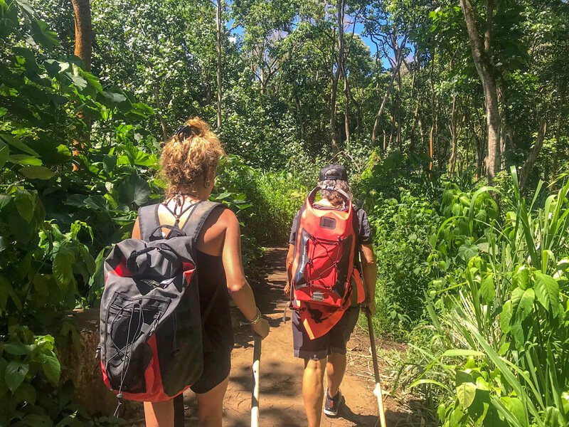 Two woman hiking with backs turned secret falls kauai