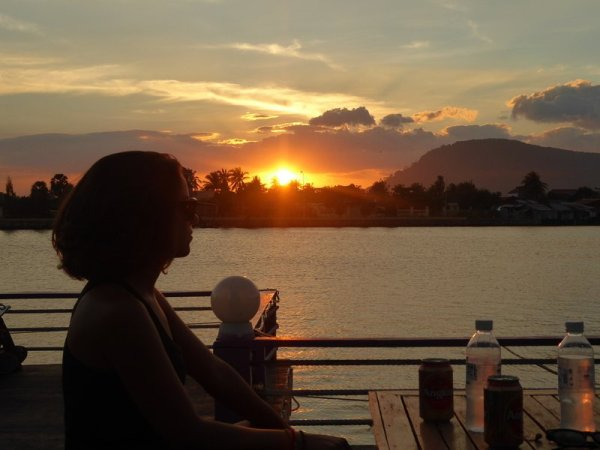 Silhouette of woman on boat in Kampot Cambodia with sunset behind the river
