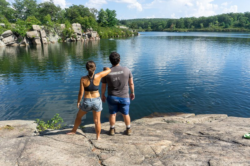 Man and woman standing on a rock backs to camera looking out at a lake