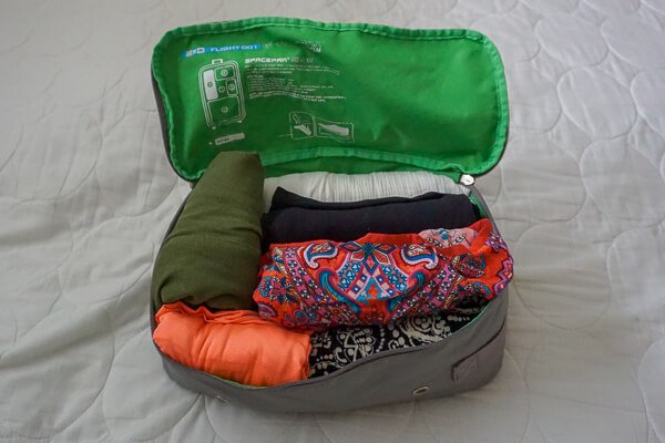 Packing cube filled with rolled women's clothing
