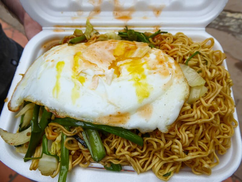 Noodles in styrofoam container with fried egg vegetable and hot sauce