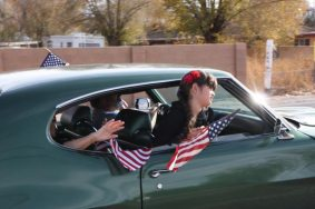 Girl leaning out car window with flag in parade