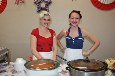 Girls in blue and red dresses in front of crock pots