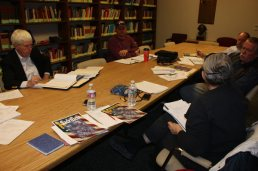 The exhibit design team meeting in room lined with books