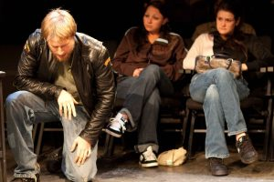 Telling Project: Man in leather jacket kneeling with two women seated behind him looking at him
