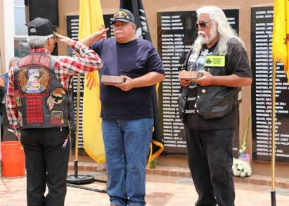 Veterans saluting while Wolfman looks on