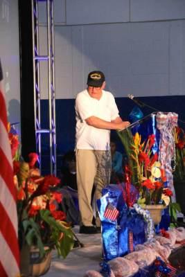 Man in veterans ballcap at podium