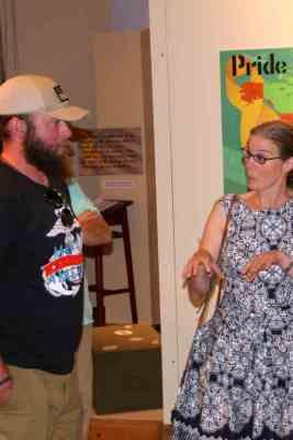Circe Olson Woessner talking to bearded man by Pride panel