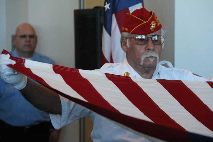 Man holding end of flag at Salute to Heroes Veterans Day Celebration 2014