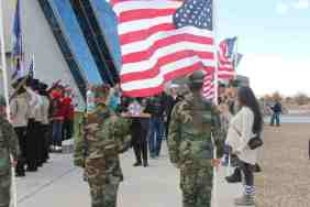 Flag line and person bearing Memorial Folded Flag outside at Salute to Heroes Veterans Day Celebration 2014