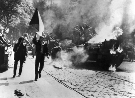 Czechoslovakian demonstrators march past a burning Soviet tank in 1968. (Image source: WikiCommons)