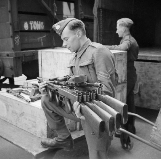 A GI un-crates a consignment of Tommy guns.