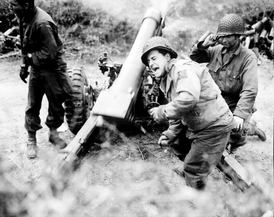 American howitzers shell German positions in France. July, 1944. One veteran of the war in Europe recalls the debilitating loudness of combat. (Image source: WikiCommons)