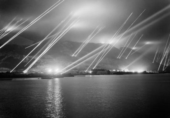 British searchlights scan the skies above Gibraltar for enemy warplanes. (Image source: WikiCommons)