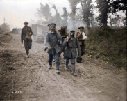 German POWs still wearing their gas masks carry casualties to a dressing station. August, 1918. (Image source Canada. Dept. of National Defence/Library and Archives Canada via the Vimy Foundation)