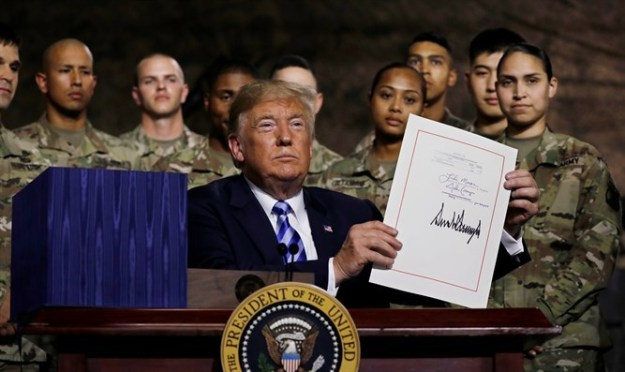 President Trump holds up the National Defense Authorization Act after signing it on Monday, August 13, 2018. The bill includes $5.5 billion to Israel.