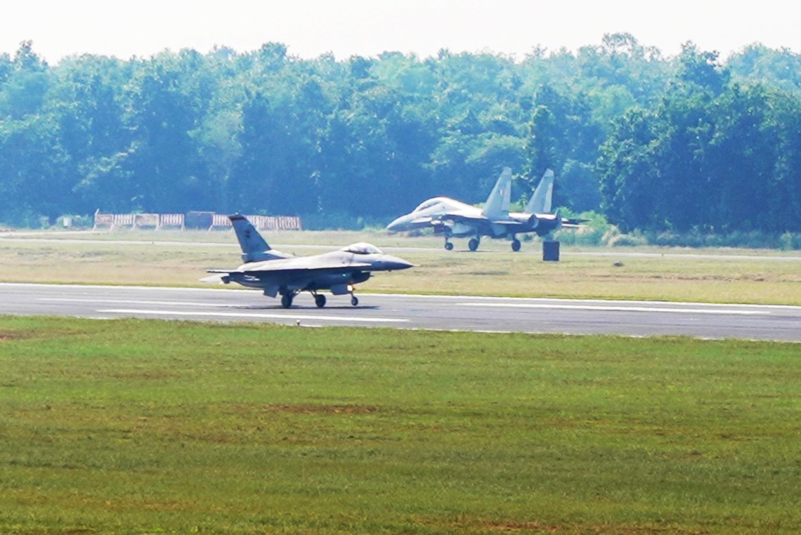 An RSAF's F-16C (foreground) and an India Air Force's (IAF) SU-30MKI fighter aircraft (background) at the Kalaikunda Air Force Station runway before take-off as part of JMT 19. Photo courtesy: MIndef