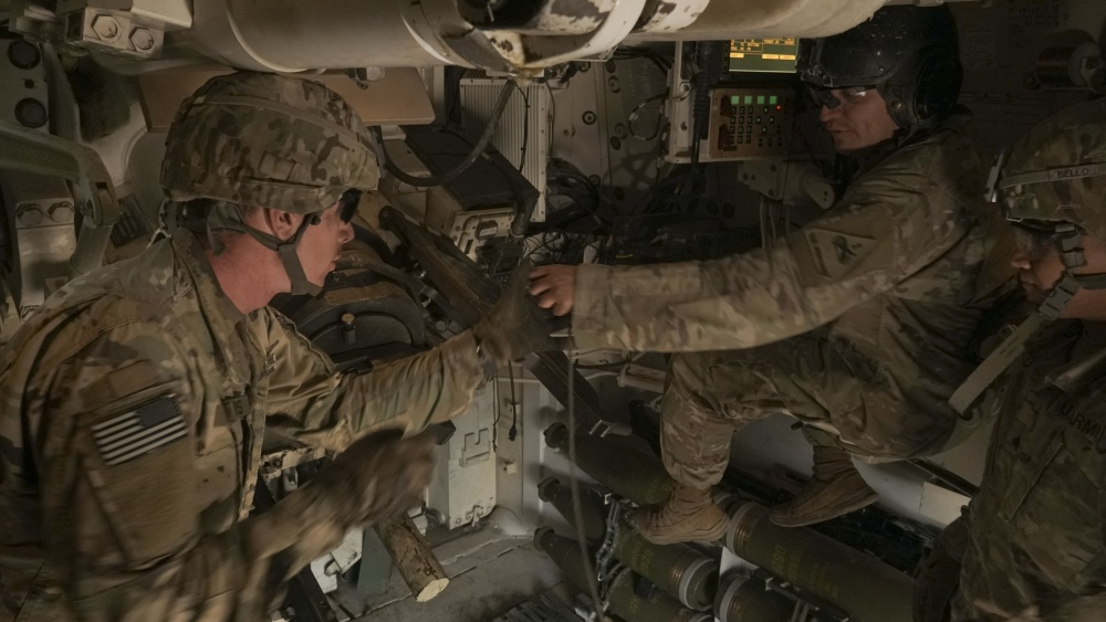"Staff Sgt. Jorge Almeraz (right), tank commander with Battery B, 4th Battalion, 2st Field Artillery Regiment, hands Spc. Joseph Sanders, a loader a lanyard after confirming a ""call for fire"" to fire nine rounds in a M109A6 Paladin during the Joint Strike Fighter Integration exercise, Nov. 7, at the Dona Ana Training Facility in New Mexico. The JSF Integration exercise tested multiple communications links between a U.S. Air Force aircraft and a U.S. Army artillery battery from the 1st Armored Division, to increase readiness across multiple domains. (U.S. Army photo by Staff Sgt. Brandon Banzhaf, 24th Theater Public Affairs Support Element)"