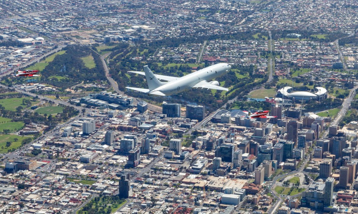 Two Air Force PC-9/A aircraft alongside a P-8A Poseidon, conduct a flypast over Adelaide, South Australia.