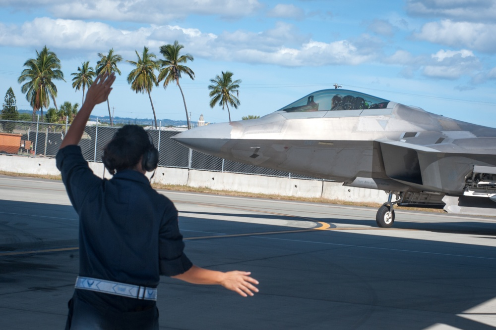 Airman 1st Class Danielle Tubania, 154th Aircraft Maintenance Squadron assistant dedicated crew chief, marshals in an F-22 Raptor Jan. 30, 2020, at Joint Base Pearl Harbor-Hickam, Hawaii.