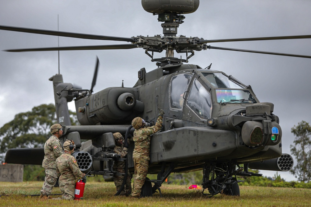 Petroleum Supply Specialists work together to refuel an Apache attack helicopter during training in FATCOW procedures.
