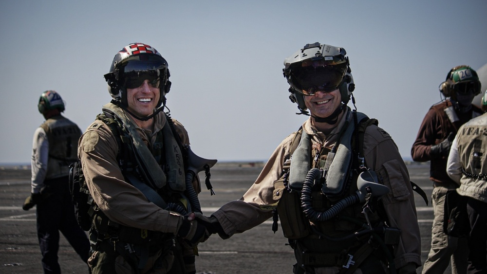 """Cmdr. Kenneth Hockycko, commanding officer of the Fighting Checkmates of Strike Fighter Squadron (VFA) 211, left, shakes hands with Capt. Robert Gentry, commander, Carrier Air Wing (CVW) 1, on the flight deck of the aircraft carrier USS Harry S. Truman (CVN 75) after Gentryâ""""¢s 1,200th career arrested landing in the Arabian Sea Feb. 1, 2020."""
