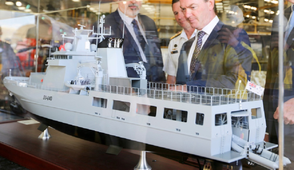 Minister for Defence, the Hon Christopher Pyne, MP (centre) inspects a model of the Arafura class offshore patrol vessel, at Osborne Naval Shipyard in Adelaide.