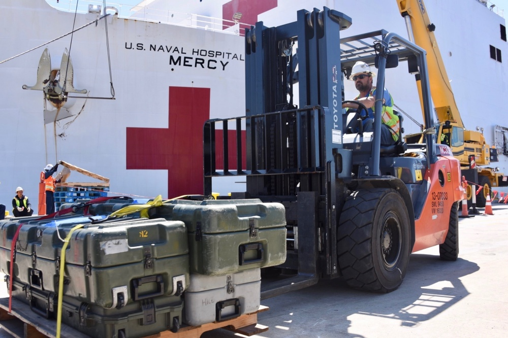 Naval Facilities Engineering Command Southwest forklift driver Steve King moves pallets of supplies to be craned aboard Military Sealift Command hospital ship USNS Mercy (T-AH 19) at Naval Base San Diego, March 21, 2020.