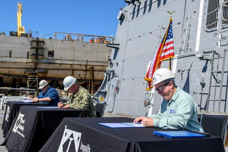 Donny Dorsey (right), Ingalls DDG 119 ship program manager; Commander Matthew McKenna (center), DDG 119 prospective commanding officer; and Peter T. Christman III, DDG 51 Project Office, SUPSHIP Gulf Coast, practice safe social distancing while signing the DD 250 transferring custody of Delbert Black (DDG 119) to the United States Navy on Friday, April 24, at Ingalls Shipbuilding in Pascagoula, Miss.