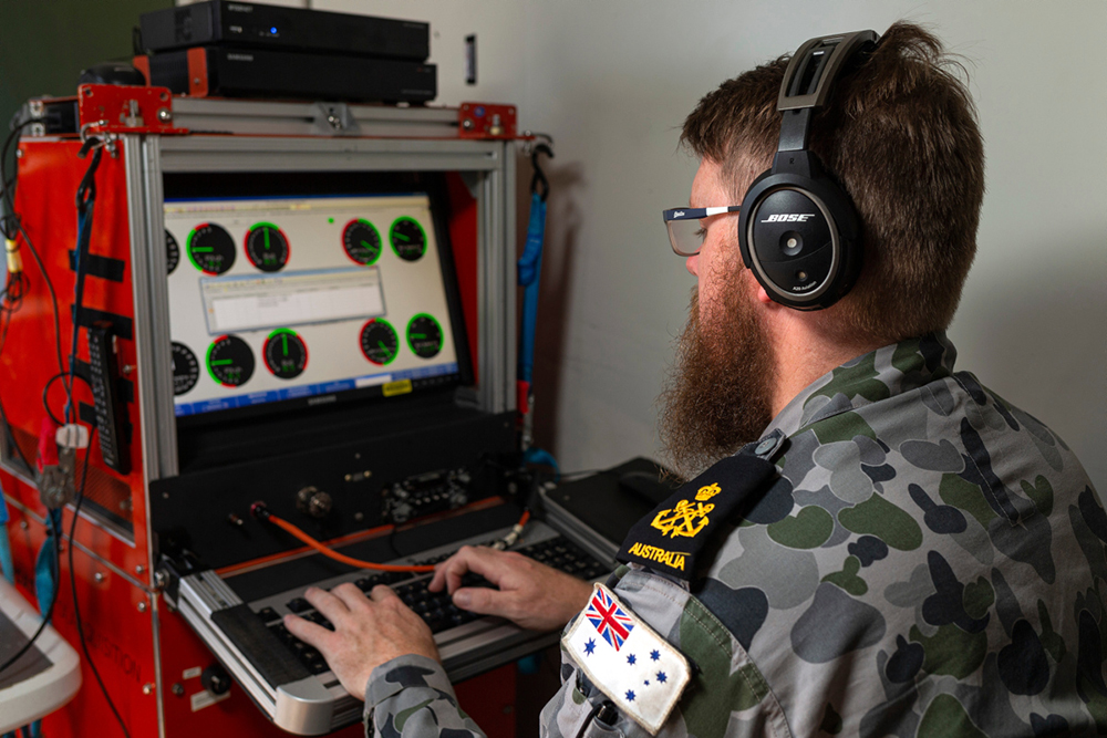 Petty Officer Aviation Technician Avionics Nicholas Simmons of the Aircraft Maintenance and Flight Trials Unit enters test flight data from an MH-60R helicopter into the computer onboard HMAS Adelaide.
