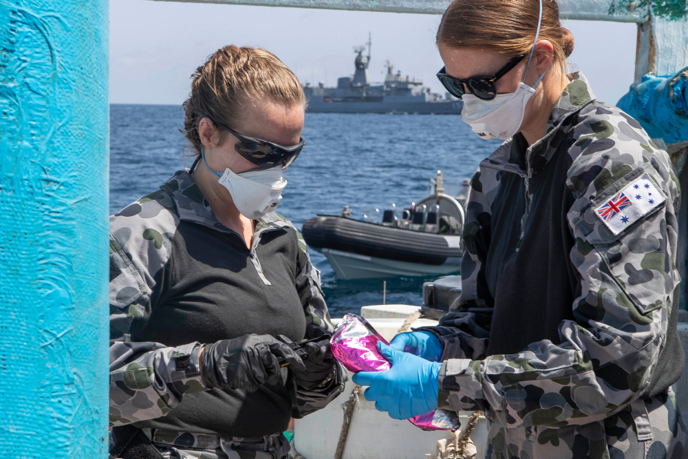 Lieutenant Maree Altham, left, and Lieutenant Shannen Rowe from HMAS Toowoomba conduct tests on a parcel discovered after boarding and searching a dhow in the Gulf of Aden as part of Operation MANITOU on 19 March 2020.