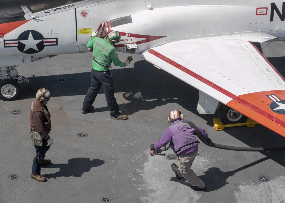 "Chief Aviation Boatswain's Mate (Fuels) Joshua Faulds, from Port Washington, Wisconsin, assigned to USS Gerald R. Ford's (CVN 78) air department, prepares to refuel a T-45C Goshawk, attached to the ""Eagles"" of Training Squadron (VT) 7, on Ford's flight deck April 7, 2020. Ford is underway in the Atlantic Ocean conducting carrier qualifications. (U.S. Navy photo by Mass Communication Specialist 2nd Class Ryan Seelbach)"