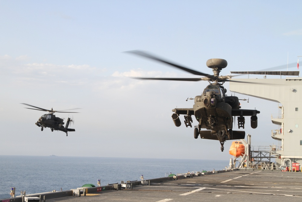 Two AH-64E Apache gunships take off from the U.S.S. Lewis B. Puller during an at sea training exercise on April 16, 2020 in the Persian Gulf. The U.S. Army and the U.S. Navy work together to not only train but also make both forces more effective. (U.S. Army photo by SGT. Andrew Winchell)