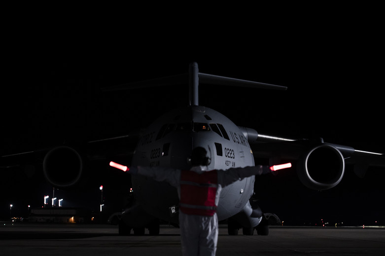 A U.S. Air Force Airman, assigned to the 721st Aerial Port Squadron, marshals a C-17 Globemaster III transporting three COVID-19 patients from Afghanistan during the first-ever operational use of the Transport Isolation System at Ramstein Air Base, Germany, April 10, 2020. The TIS is an infectious disease containment unit designed to minimize contamination risk to aircrew and medical attendants, while allowing in-flight medical care for patients afflicted by a disease—in this case, COVID-19. (U.S. Air Force photo by Staff Sgt. Devin Nothstine)