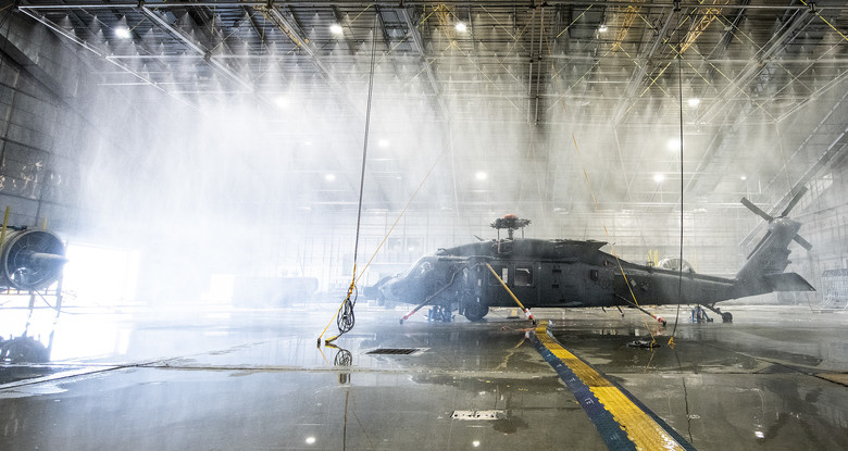 An HH-60W Jolly Green gets hit with 45 mph winds and drenched under 130 gallons-per-minute rain in the McKinley Climatic Lab April 1 at Eglin Air Force Base, Fla.  The Air Force's new search and rescue helicopter and crews experienced temperature extremes from 120 to -60 degrees Fahrenheit as well as torrential rain during the month of testing.  The tests evaluate how the aircraft and its instrumentation, electronics and crew fare under the extreme conditions it will face in the operational Air Force.  (U.S. Air Force photo/Samuel King Jr.)