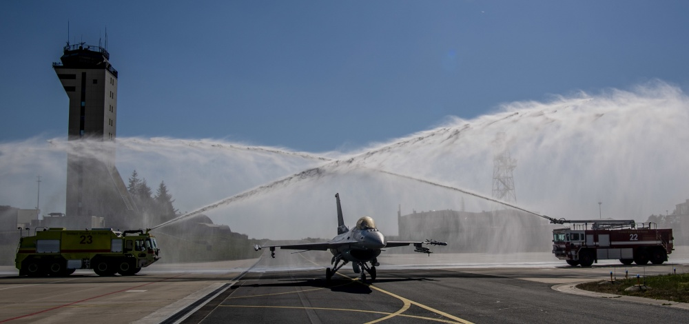 U.S. Air Force members from the 52nd Civil Engineer Squadron perform a water salute for aircraft 343, a F-16 Fighting Falcon assigned to the 52nd Fighter Wing at Spangdahlem Air Base, Germany, April 23, 2020. The water salute was in celebration of the aircraft completing 10,000 flight hours. Aircraft 343 became the first F-16 to cross the 10,000 flight hour mark in U.S. Air Forces in Europe-Air Forces Africa history. (U.S. Air Force photo by Senior Airman Kyle Cope)