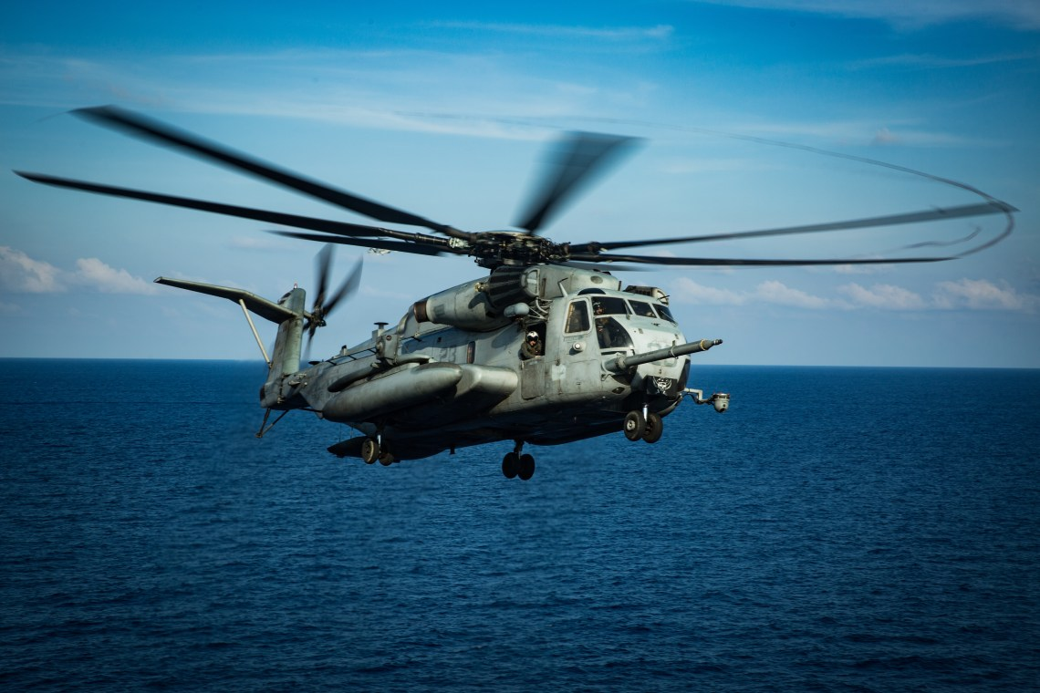 A CH-53E Super Stallion helicopter with Marine Medium Tiltrotor Squadron (VMM) 265 (Reinforced), 31st Marine Expeditionary Unit (MEU), lands on the flight deck of amphibious assault ship USS America (LHA 6) during flight operations. Marines and Sailors aboard the America regularly conduct flight operations while underway to maintain their readiness to respond to contingencies. America, flagship of the America Expeditionary Strike Group, 31st MEU team, is operating in the U.S. 7th Fleet area of operations to enhance interoperability with allies and partners and serve as a ready response force to defend peace and stability in the Indo-Pacific region. (U.S. Marine Corps photo by Sgt. Audrey M. C. Rampton)