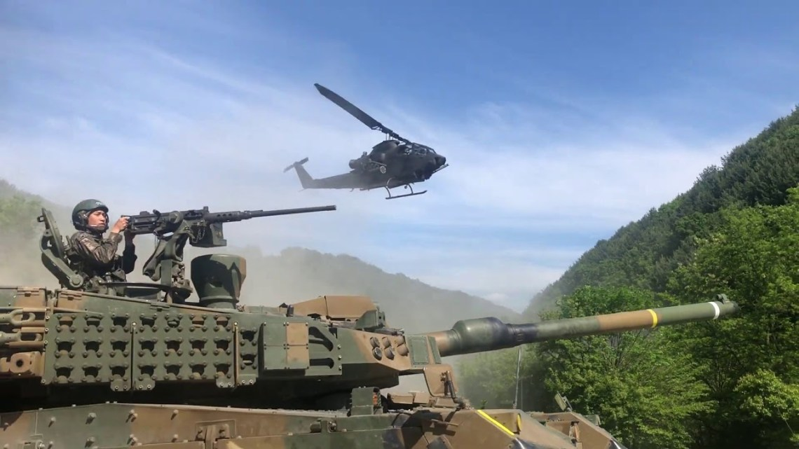 Republic of Korea Army AH-1S Cobra attack helicopters provide air cover for K2 Black Panther main battle tanks.