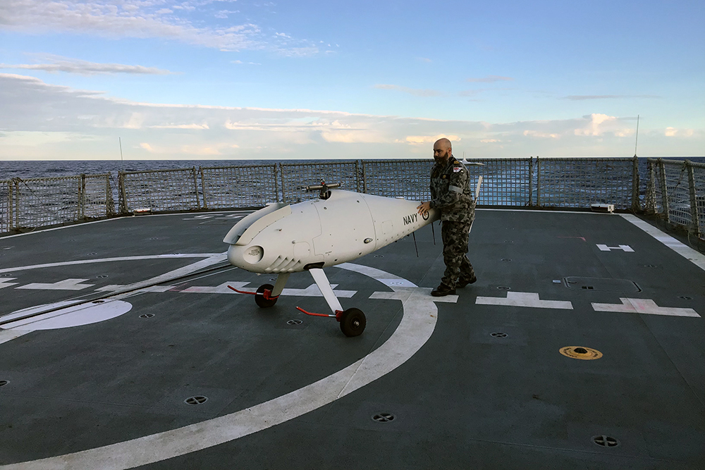 822X Squadron Deputy Engineer Lieutenant Gareth Forbes recovers the S-100 Camcopter on HMAS Ballarat's flight deck.
