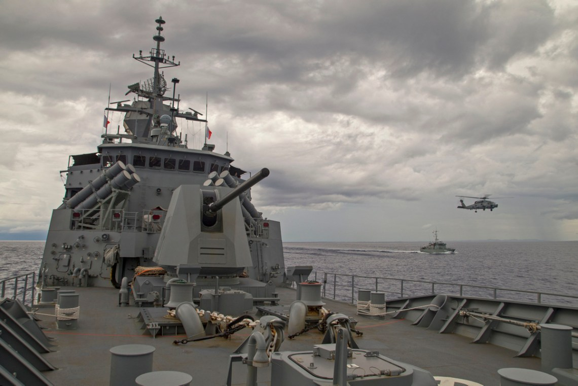 HMAS Parramatta's embarked MH-60R Helicopter flies between the two ships in the waters of Yap, Micronesia.