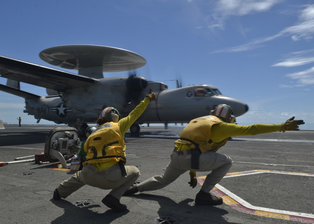 "Lt. Kristin Hope, from Ogden, Utah, left, and Lt. Michael Watson, from Elverson, Pennsylvania, signal an E-2D Hawkeye, assigned to the ""Tigertails"" of Carrier Airborne Early Warning Squadron (VAW) 125, to launch in support of flight operations, aboard the aircraft carrier USS Ronald Reagan (CVN 76)."