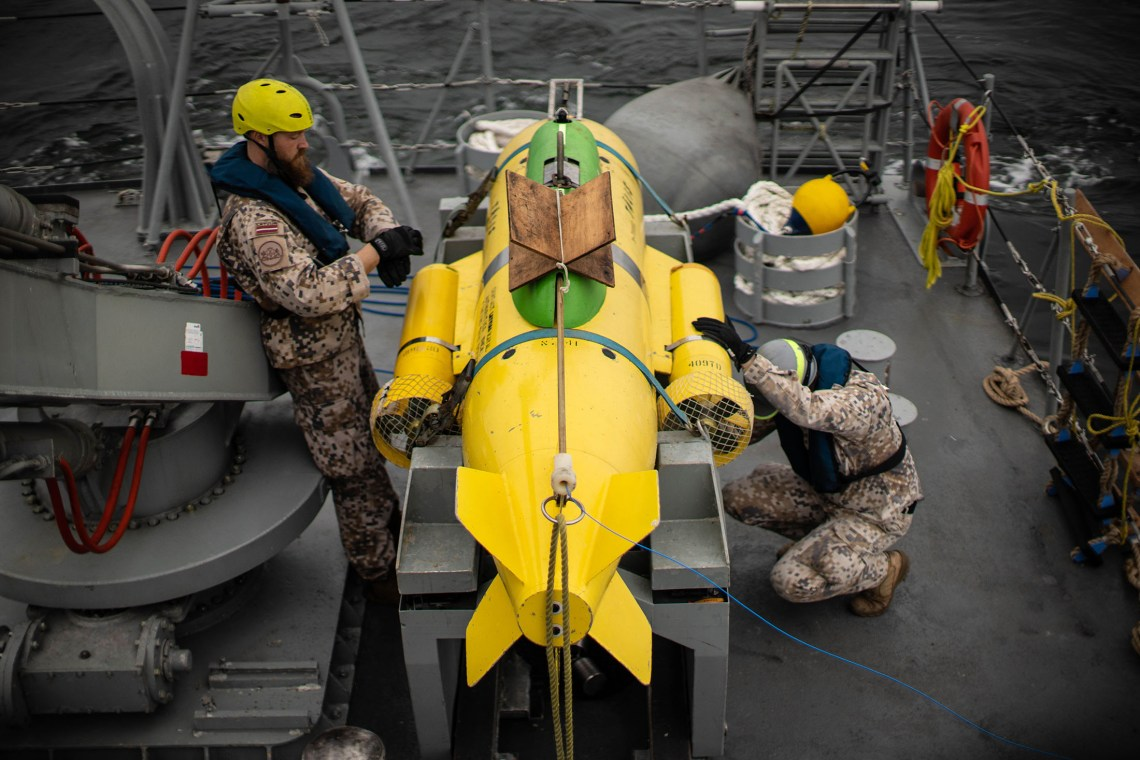 Crewmembers from the LVNS Tālivaldis with the ship's ROV (remote operated vehicle) PAP 104, an underwater robot that helps identify and dispose of mines or unexploded ordnance.