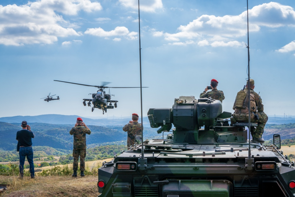 An AH-64 Apache from A Co, 1-3 Attack Reconnaissance Battalion make a low pass over German joint terminal attack controller instructors and members of the Franco-German Brigade at the end of a successful training iteration on Sep. 9 at Baumholder Training Area, Germany.