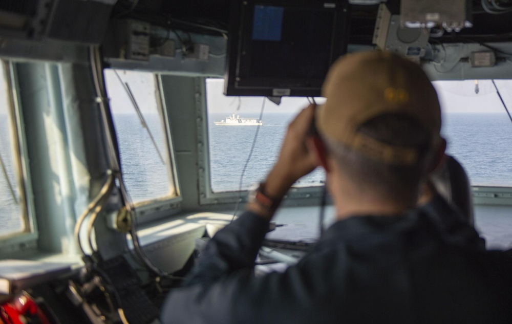 Cmdr. Robert Watts, commanding officer of the guided-missile destroyer USS John Paul Jones (DDG 53), monitors the area during a passing exercise with the Royal Bahrain Naval Force ship Al Manama (P 50) in the Persian Gulf, Oct 27.