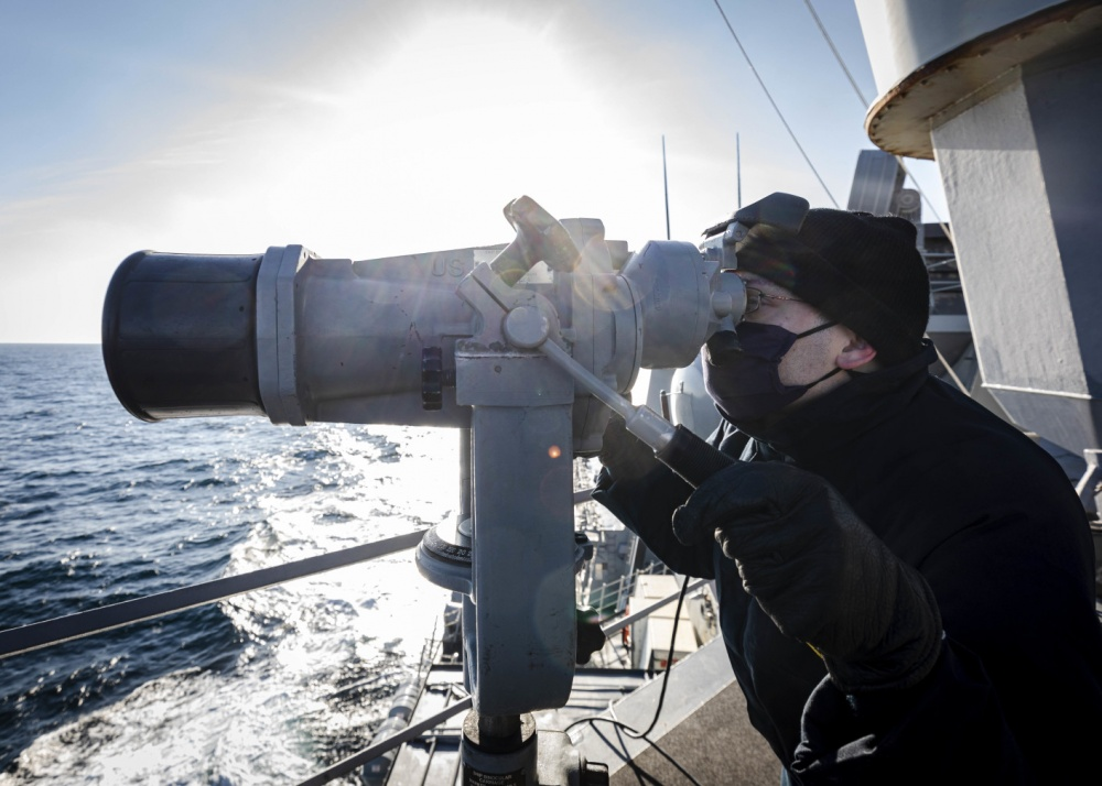 Ensign James Bateman, from Huntsville, Ala., scans the horizon utilizing the 'big eyes' while standing watch on the on the bridge wing as the guided-missile destroyer USS John S. McCain (DDG 56) conducts routine underway operations.