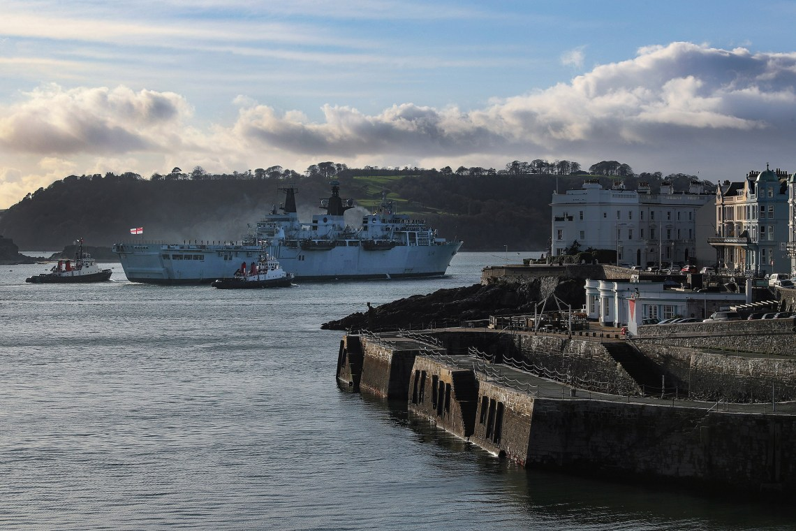 Shepherded by two tugs Royal Navy HMS Albion (L14) passes Plymouth's Grand Parade