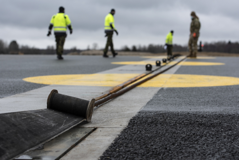 """U.S. Air Force Airman 1st Class Chelsea Glasscock, 435th Construction and Training Squadron Aircraft Arresting System Depot apprentice, works with Ã""""mari Air Base personnel to return the system to its starting position during a Barrier Arresting Kit certification at Ã""""mari AB, Estonia, March 17, 2021."""