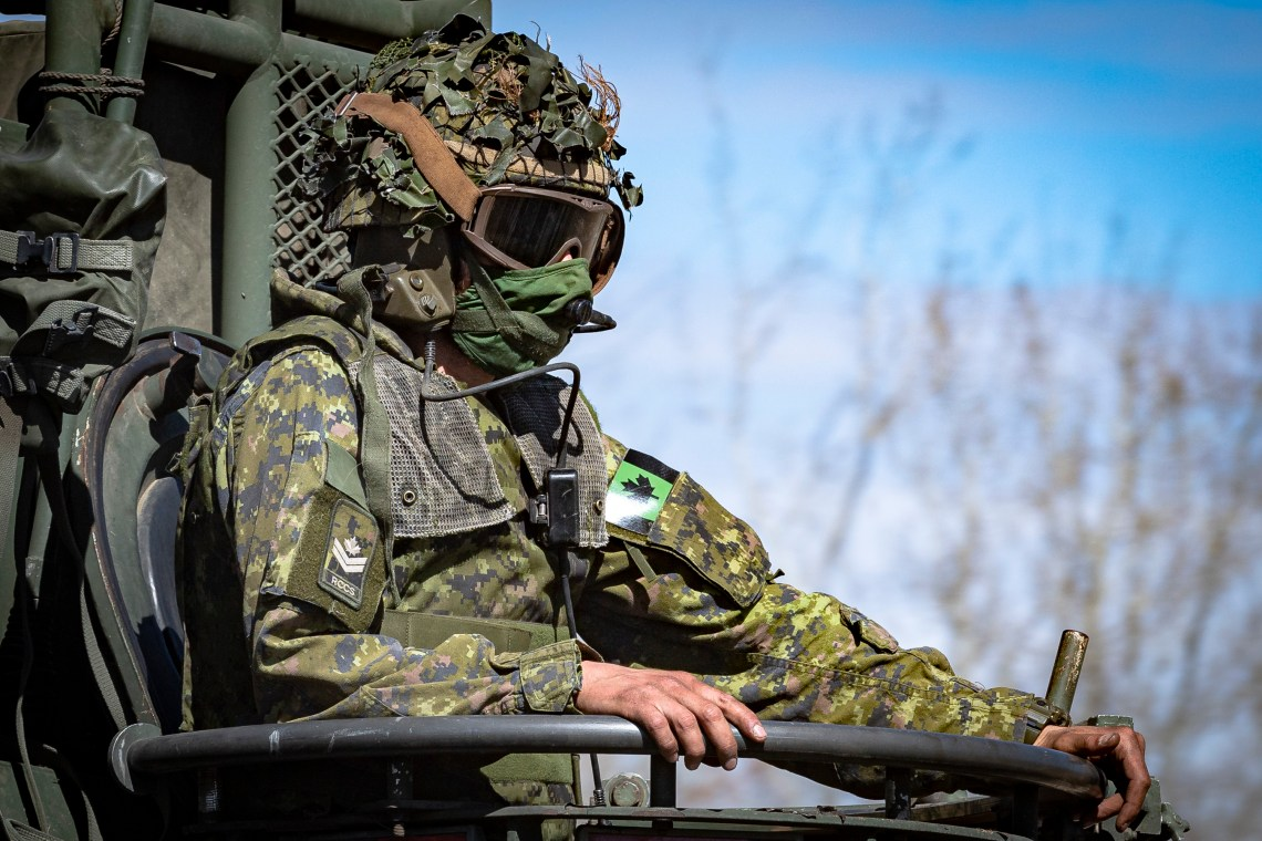 A Master Corporal from the Royal Canadian Corps of Signalsrides on a Light Armoured Vehicle (LAV) III while in the training area at 3rd Canadian Division Support Base Garrison Wainwright in preparation for Exercise MAPLE RESOLVE 21 on April 30, 2021.