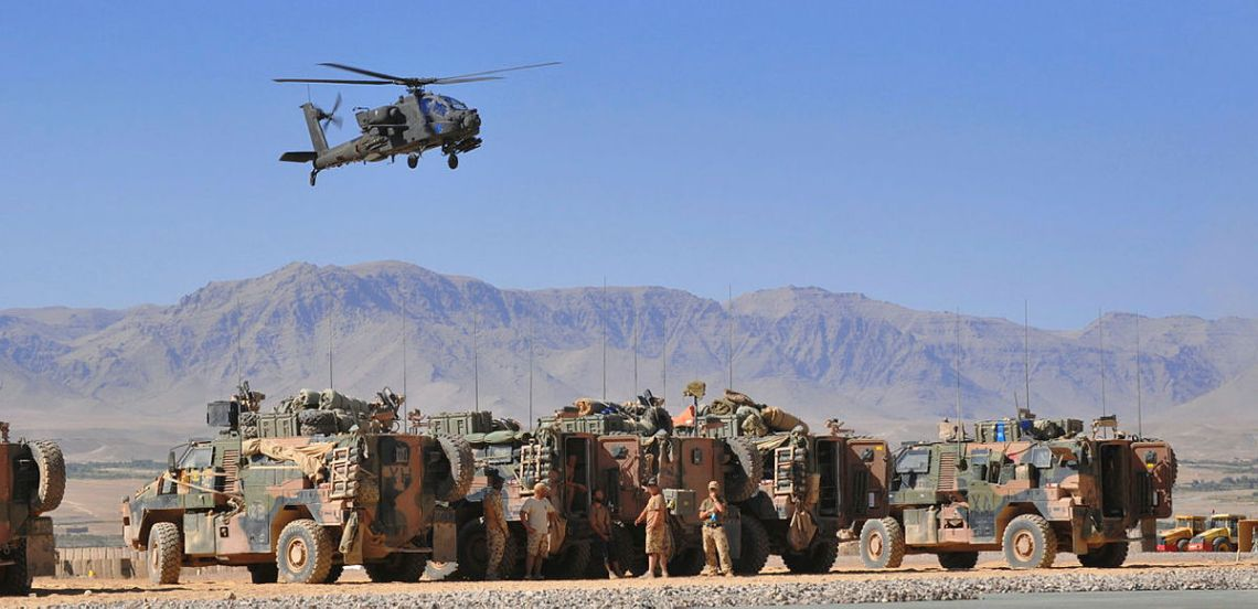 A Dutch Ah-64 Apache attack helicopter flies over waiting Bushmaster transport at Tarin Kowt following the completion of a mission.