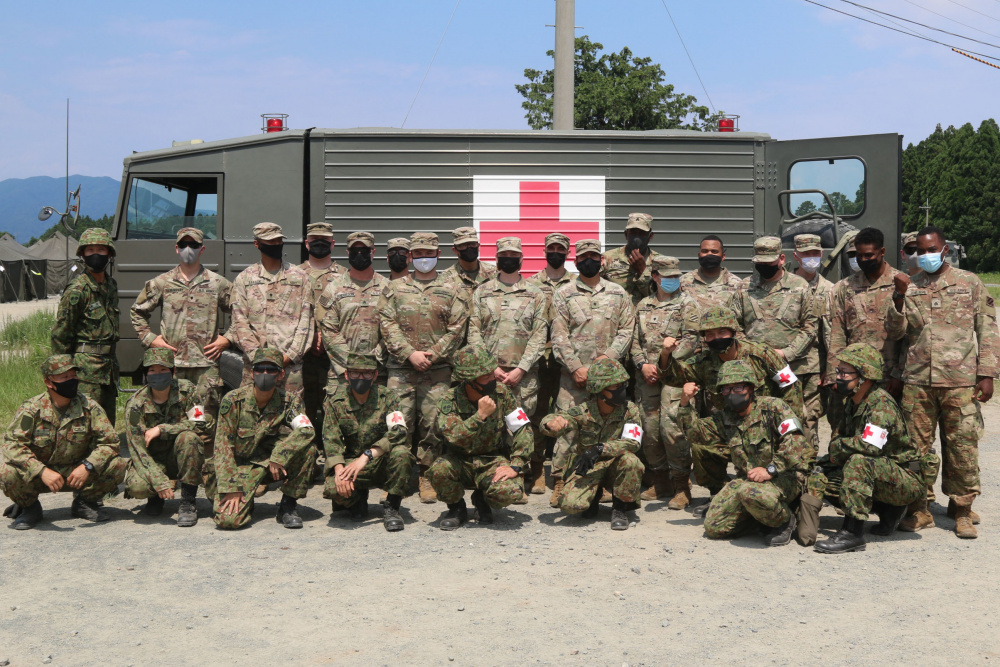 Medics assigned to 1st Battalion, 28th Infantry Regiment, 3rd Infantry Division, pose alongside medics from the Japan Ground Self-Defense Force after training on how to properly load a casualty into an ambulance during bilateral medical training on Aibano Training Area, Japan, as part of exercise Orient Shield 21-2 June 24, 2021.